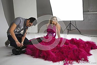 Fashion stylists adjusts model s footwear in studio