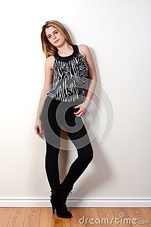 Fashion teen model leaning on wall
