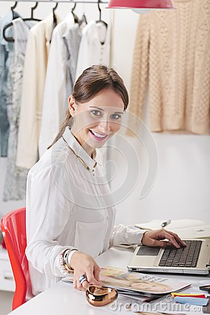 Fashion woman blogger working in a creative workspace.