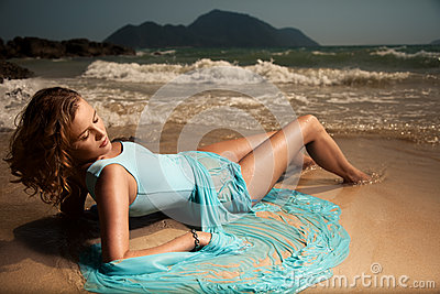 Fashion Woman In Blue Dress Lying On Sand Tropical B