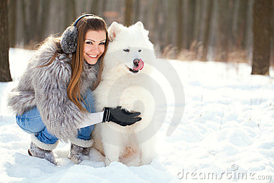 Fashion woman with dog samoyed in winter forest