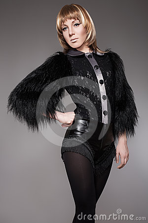 Fashion woman in luxury fur jacket, leather shorts