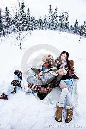 Fashion women lying on white snow winter background fisheye