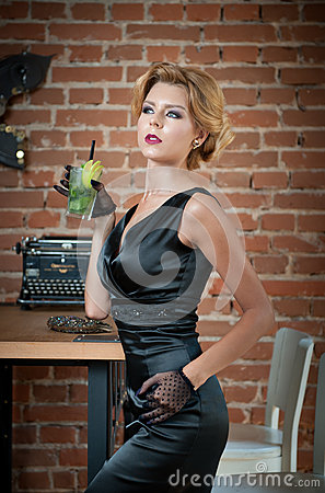 Free Fashionable Attractive Lady With Little Black Dress And Gloves Standing Near A Table In Restaurant Holding A Glass Of Drink Stock Images - 90581124