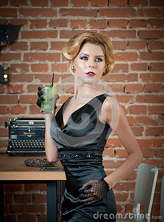Free Fashionable Attractive Lady With Little Black Dress And Gloves Standing Near A Table In Restaurant Holding A Glass Of Drink Stock Images - 90581134