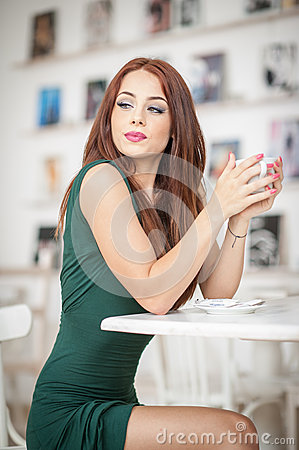 Free Fashionable Attractive Young Woman In Green Dress Sitting In Restaurant. Beautiful Redhead Posing In Elegant Scenery With A Coffee Royalty Free Stock Photography - 47646147