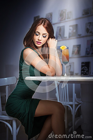 Free Fashionable Attractive Young Woman In Green Dress Sitting In Restaurant. Beautiful Redhead Posing In Elegant Scenery With A Drink Stock Photography - 43365712