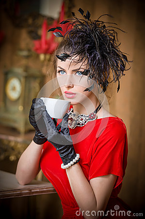 Free Fashionable Attractive Young Woman In Red Dress Drinking Coffee In Restaurant. Beautiful Brunette In Elegant Vintage Scenery Royalty Free Stock Photo - 43464545