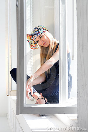Fashionable blonde at the opened window