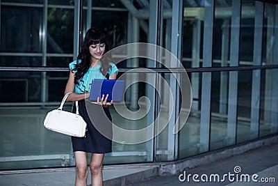 Fashionable businesswoman working on laptop