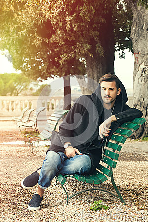 Free Fashionable Cool Young Man Relaxing On A Bench In A Park With Trees Stock Image - 69233551