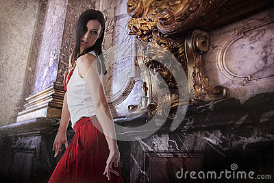 Fashionable female model dancing indoors, baroque style interior