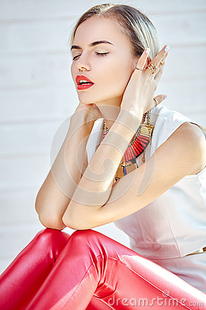 Fashionable girl sitting in red leather pants and white top Stock Photo