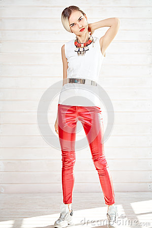 Fashionable girl standing in red leather pants and white top Stock Photo