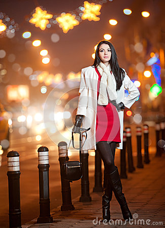 Fashionable lady wearing red dress and white coat outdoor in urban scenery with city lights in background. Full length portrait