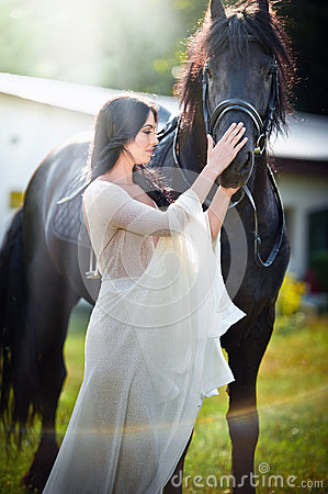 Free Fashionable Lady With White Bridal Dress Near Brown Horse. Beautiful Young Woman In A Long Dress Posing With A Friendly Horse Royalty Free Stock Images - 58036749