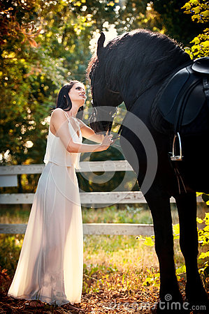 Free Fashionable Lady With White Bridal Dress Near Brown Horse In Nature. Beautiful Young Woman In A Long Dress Posing With A Horse Stock Photos - 58036753