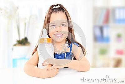 Fashionable little girl holding a baby bottle full of milk