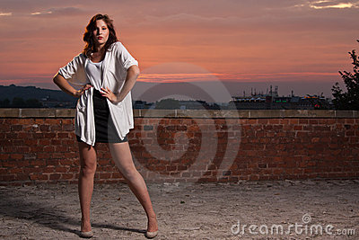 Fashionable model posing, dramatic sunset backgrou
