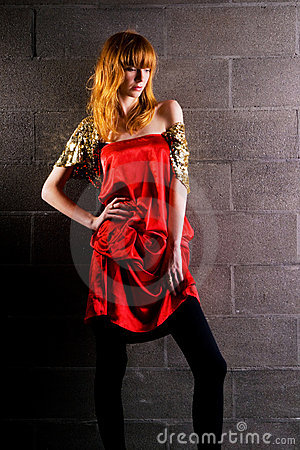 Fashionable red-haired woman in a satin red dress