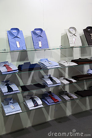 Fashionable shirts with ties lie on shelves