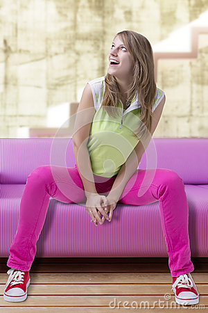 Amazed young woman sitting in pose on a coach