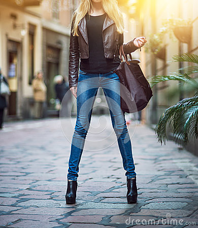 Free Fashionable Young Blonde Girl With Long Legs Wearing Blue Jeans, Leather Brown Coat And Holding A Bag Walking And Shopping On City Stock Images - 81503434