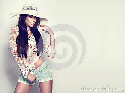 Fashionable young brunette girl posing in white hat.