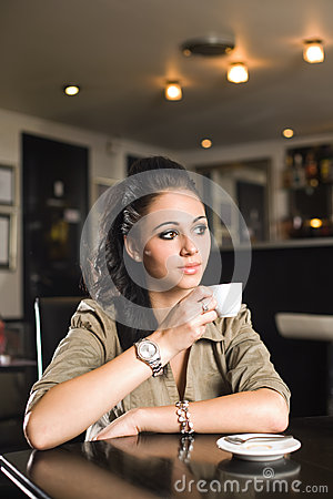 Fashionable young brunette woman having coffee.