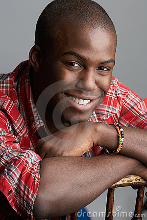 Fashionable Young Man Resting On Chair In Studio