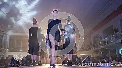 Fasonuje tydzień przy heeled w identycznych czarnych przejrzystych sukniach z eleganckimi torebkami, grupowi podium modele iść da zbiory wideo