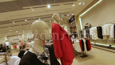 Fast Motion across Store and Focus on Mannequin in Red Jacket. Fast motion across big fashion store with new stylish clothes shoes and accessories and focus on stock video