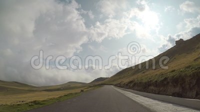 Fast timelapse POV of driving car on curving route with hills and cloudy sky on a mountain toppov -. Fast timelapse POV of driving car on curving route with stock footage