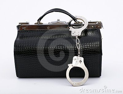 Fastened handcuffs pinned to black bag