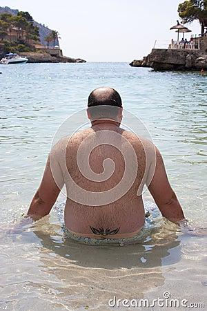 Fat man on the beach