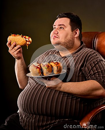 Fat man eating fast food hot dog. Breakfast for overweight person. Stock Photo