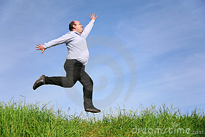 Fat man jumps on meadow