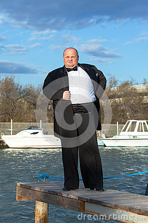 Fat man in tuxedo on pier