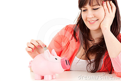 Fat teenage girl putting euro coin in piggy bank