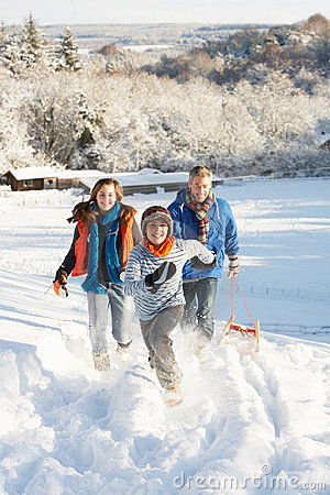 Free Father And Children Pulling Sledge Up Snowy Hill Royalty Free Stock Photo - 14189085