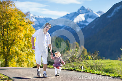 Father with baby on road between snow mountains