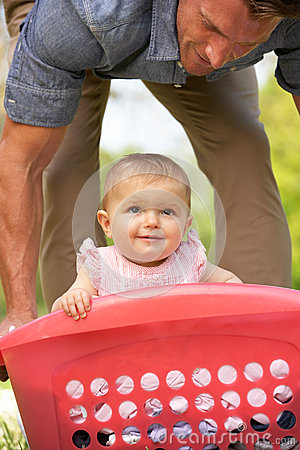 Father Carrying Baby Girl In Laundry Basket