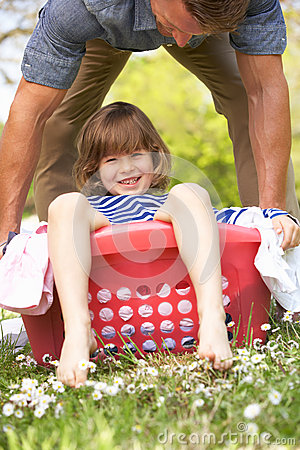 Father Carrying Son Sitting In Laundry Basket