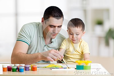 Father and child paint together. Dad teaches son how to paint correct and beautiful on paper. Family creativity and Stock Photo