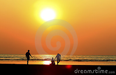 father and  child by the sea shore, sunset