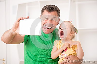 Father and child using electronic tablet at home