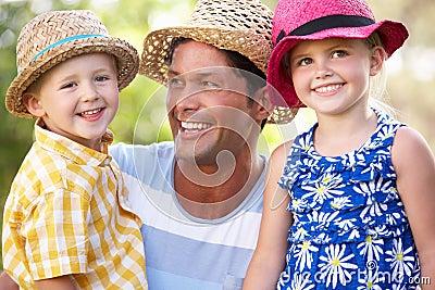 Father And Children Relaxing In Summer Garden