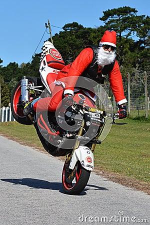 Free Father Christmas Doing Front Wheel Wheelie Stock Photo - 72867780