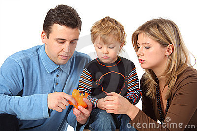 Father cleans to son an orange