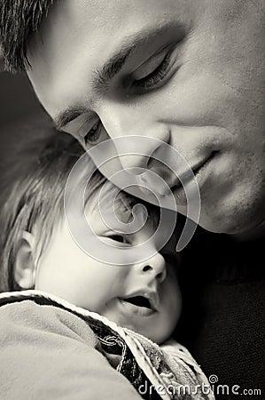 Father cuddling baby son